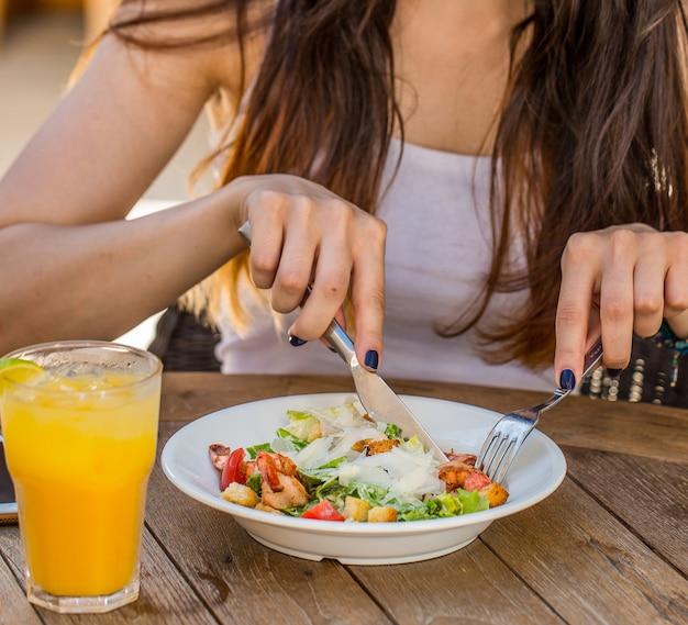 Mulher comendo salada caesar com um copo de suco de laranja fresco