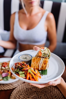 Mulher comendo salada colorida de refeição vegetariana vegana saudável na luz do dia natural do café de verão