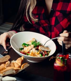 Mulher comendo salada de frango com legumes cozidos