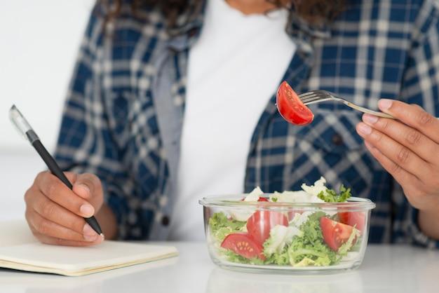 Mulher comendo salada e escrevendo no caderno