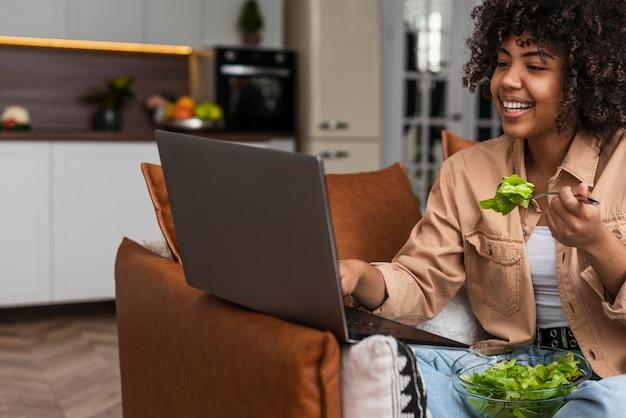 Mulher comendo salada e olhando no laptop