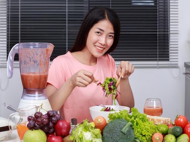Mulher comendo salada na cozinha