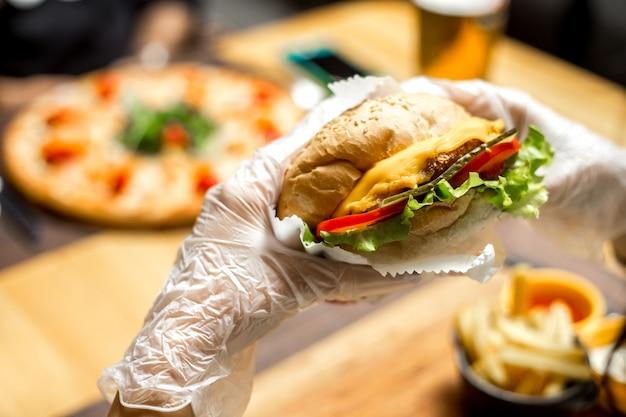 Mulher comendo sanduíche com queijo e tomate