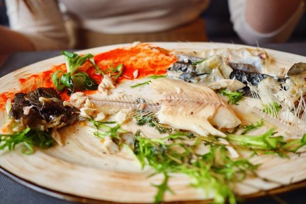 Mulher comendo sobras de peixe com garfo e faca em um café, close-up