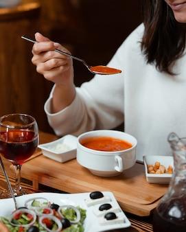 Mulher comendo sopa de tomate com recheio de pão, um copo de vinho