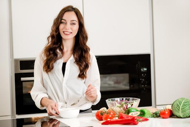 Mulher comendo sopa na cozinha onde ela cozinha legumes