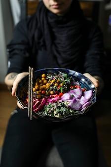 Mulher comendo tigela de buda orgânico no almoço