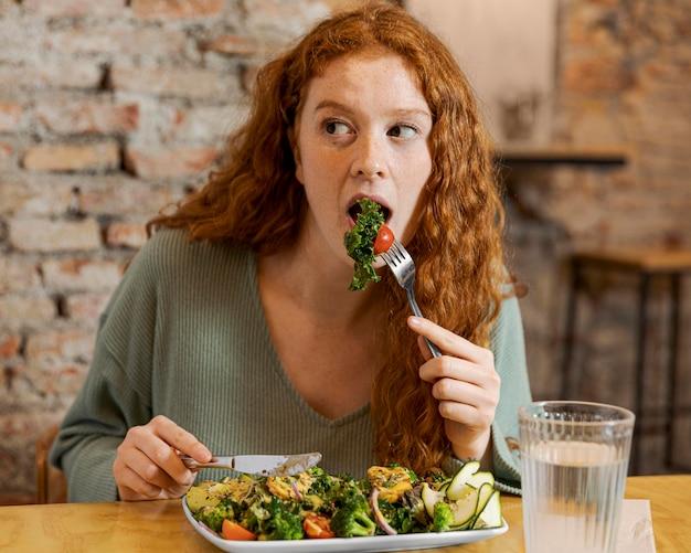 Mulher comendo tiro médio