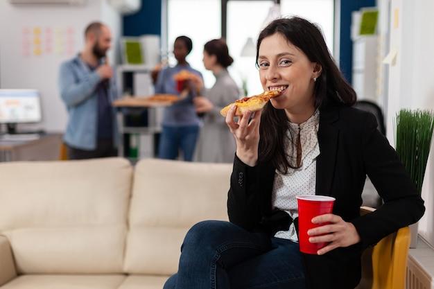 Mulher comendo uma fatia de pizza em uma festa depois do trabalho com amigos