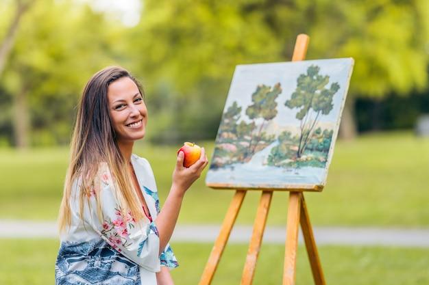 Mulher comendo uma maçã sentada em frente a uma tela pintada em um parque.
