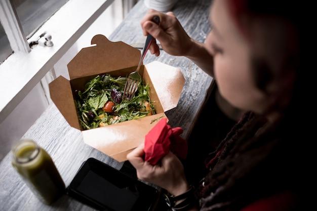 Mulher comendo uma salada no café