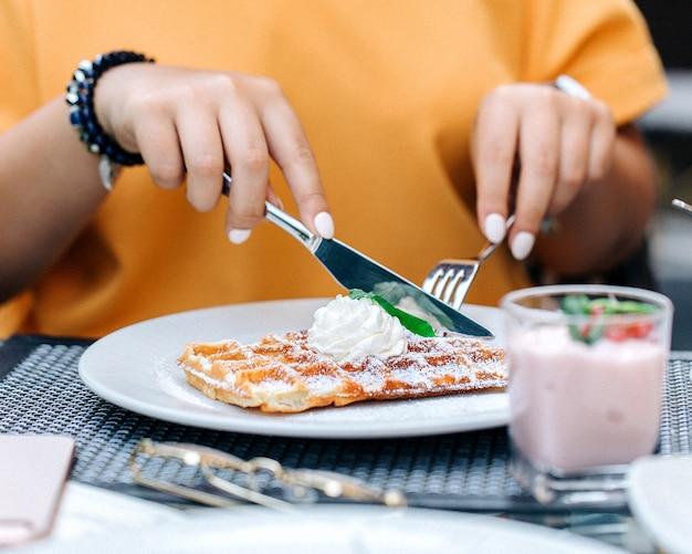 Mulher comendo waffles cobertos com creme 1