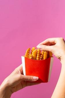 Mulher, comer, batatas fritas, de, caixa vermelha