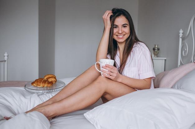 Mulher, comer, delicioso, croissant, com, café cama