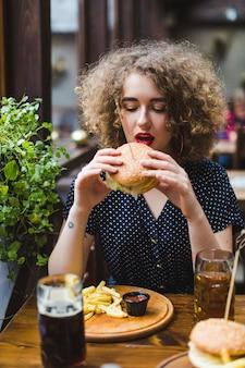 Mulher, comer, hamburger, em, restaurante