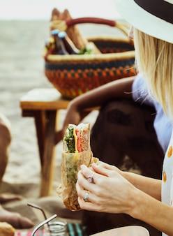 Mulher, comer, um, sanduíche, em, um, piquenique praia