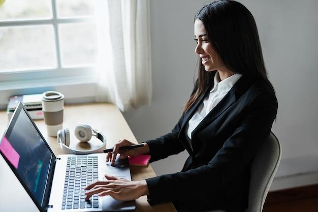 Mulher, comerciante de negócios fazendo pesquisa de blockchain dentro do escritório de fundos de hedge - foco no rosto