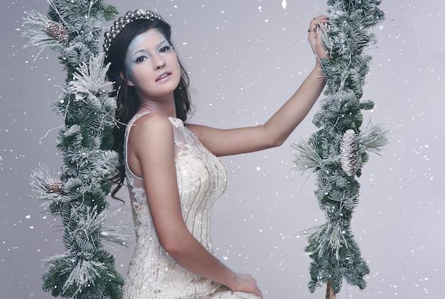 Mulher como a rainha da neve no balanço
