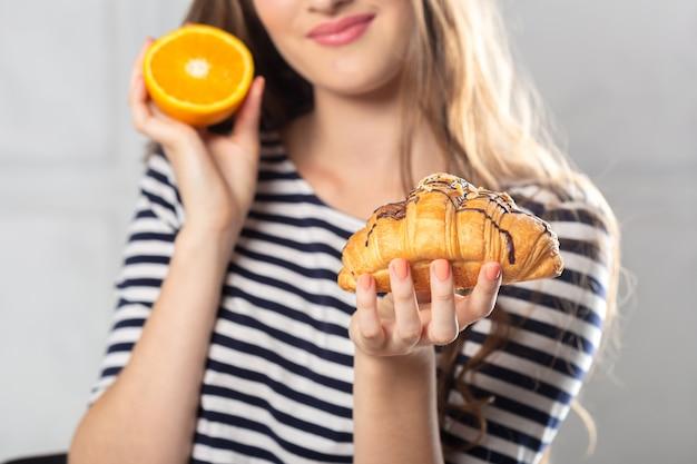 Mulher, comparando, insalubre, bolo, e, laranja, fruta