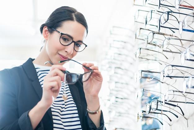 Mulher, comparando, óculos, em, oculista