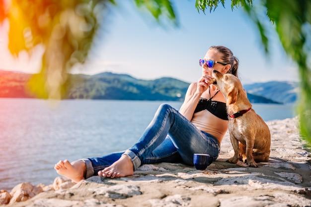 Mulher compartilhando biscoitos com seu cachorro