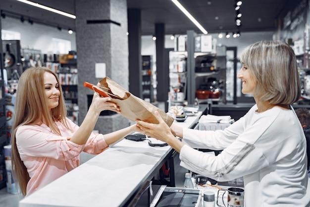 Mulher compra pratos na loja