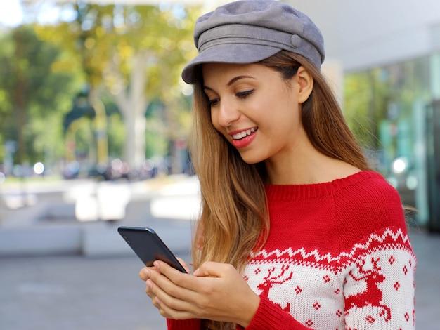 Mulher compradora de natal comprando online no telefone inteligente em shopping center.
