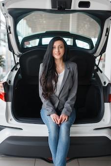Mulher comprando carro novo, senhora perto do porta-malas aberto