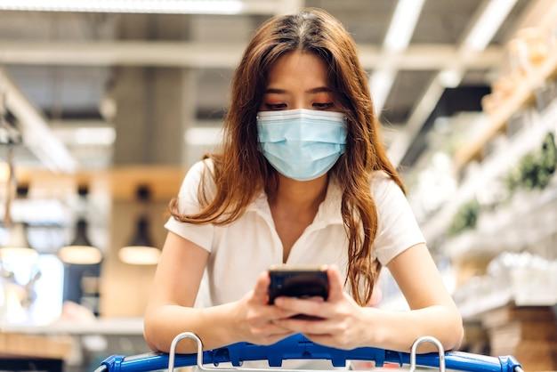 Mulher comprando e usando smartphone na loja