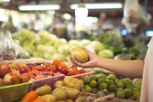 Mulher comprando frutas e legumes orgânicos