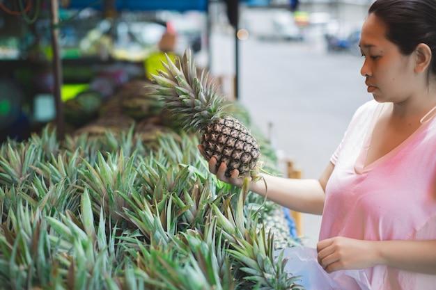 Mulher comprando frutas orgânicas