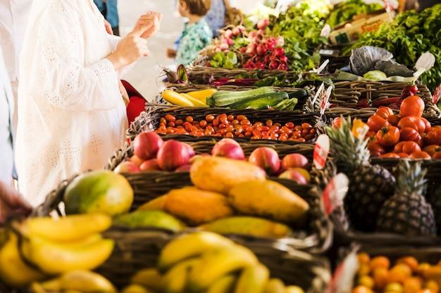 Mulher comprando legumes e frutas no mercado dos fazendeiros