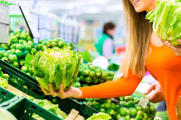 Mulher, comprando, legumes, em, supermercado