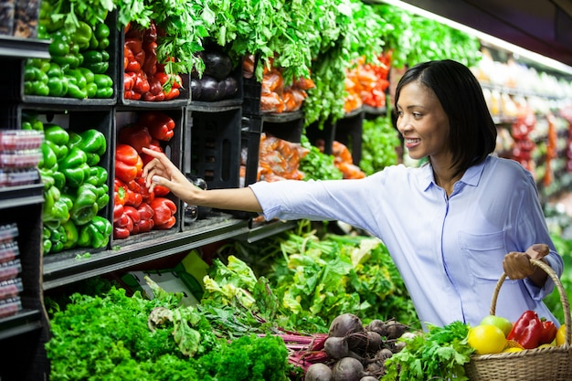 Mulher comprando legumes na seção orgânica