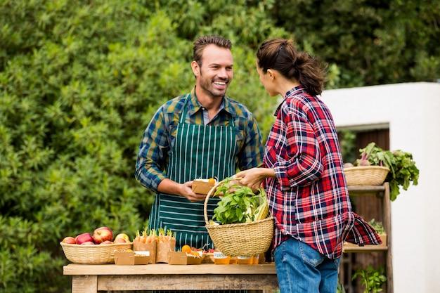 Mulher comprando legumes orgânicos do homem