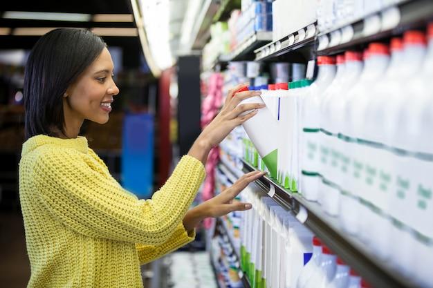 Mulher comprando leite da seção de laticínios