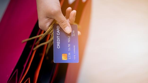 Mulher comprando muitos produtos durante a venda. pague pelos produtos do cartão de crédito durante a temporada de férias.
