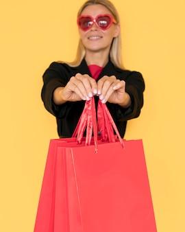 Mulher comprando na sexta feira negra mostrando sacolas vermelhas