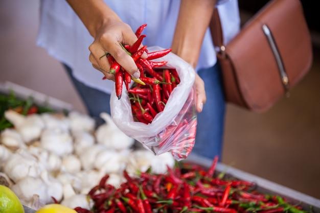 Mulher comprando pimentões vermelhos