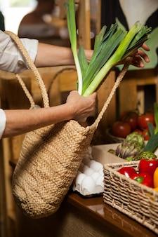 Mulher comprando vegetais folhosos na seção orgânica