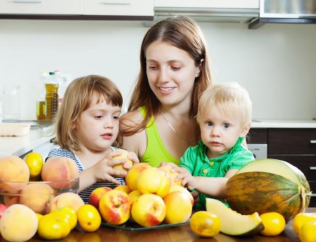 Mulher comum com filhas comendo frutas