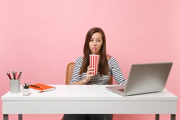 Mulher concentrada bebendo do copo de plástico com refrigerante de cola, trabalhando no projeto no escritório na mesa branca com laptop pc contemporâneo isolado no fundo rosa. carreira empresarial de realização. copie o espaço.