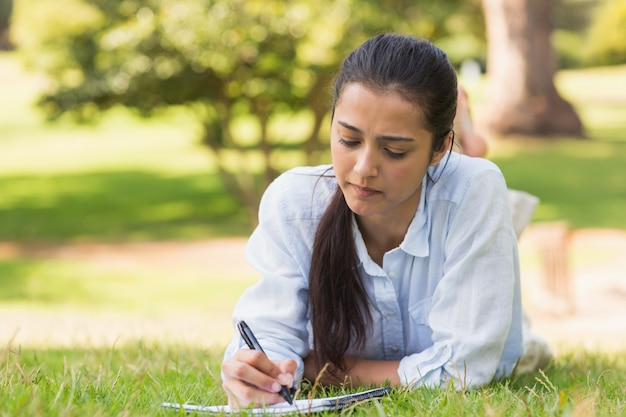 Mulher concentrada com livro e caneta no parque