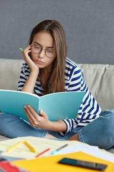 Mulher concentrada de óculos, pensa em ideias criativas para publicação, segura caneta