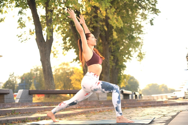 Mulher concentrada desportiva praticando ioga, em pose de anjaneyasana, malhando no parque ao pôr do sol.