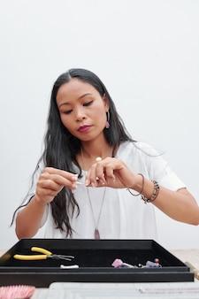 Mulher concentrada em fazer brincos