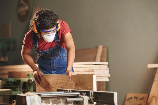 Mulher concentrada em macacão jeans, óculos de proteção e protetores de ouvido processando prancha de madeira em máquina de trabalhar madeira