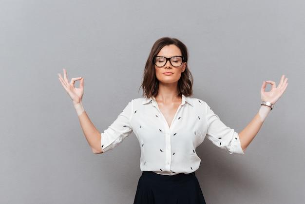 Mulher concentrada em óculos e maditation de roupas de negócios no estúdio em cinza