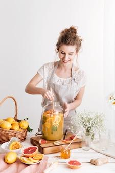 Mulher concentrada em pé dentro de casa cozinhar bebidas cítricas