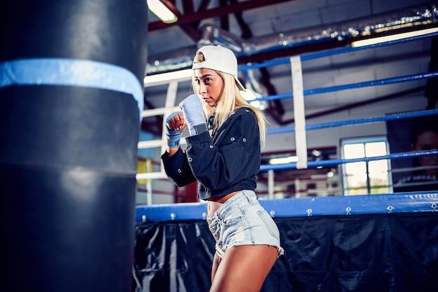 Mulher concentrada fazendo um treino de boxe fitness com um saco de pancadas.